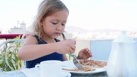 Το μικρό κορίτσι κόβει μια τηγανίτα και την τρώει για το πρόγευμα φιλμ μικρού μήκους