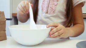 Το μικρό κορίτσι μαθαίνει να μαγειρεύει στην κουζίνα και να κάνει το αρτοποιείο χρησιμοποιώντας το lap-top απόθεμα βίντεο