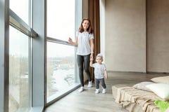 Το μικρό κορίτσι μαθαίνει να περπατά με το mom της στοκ φωτογραφίες