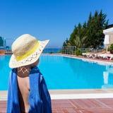 Το μικρό κορίτσι με μια μπλε πετσέτα και ένα καπέλο αχύρου στέκεται με την πίσω και εξετάζει τη λίμνη στοκ φωτογραφίες με δικαίωμα ελεύθερης χρήσης