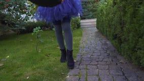 Το μικρό κορίτσι με το τέχνασμα ή μεταχειρίζεται την τσάντα περπατώντας στους γείτονες για τις καραμέλες, αποκριές απόθεμα βίντεο