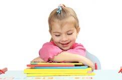 Το μικρό κορίτσι με τα βιβλία σε έναν πίνακα Στοκ Εικόνες