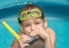 Το μικρό κορίτσι με τα προστατευτικά δίοπτρα και κολυμπά με αναπνευτήρα Στοκ Φωτογραφία