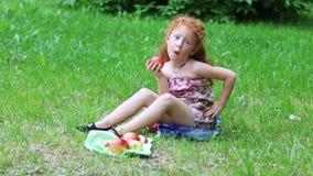 Το μικρό κορίτσι με την κόκκινη τρίχα τρώει το μήλο στο χορτοτάπητα στο πράσινο θερινό πάρκο απόθεμα βίντεο