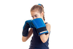Το μικρό κορίτσι με την πλεξίδα στέκεται στα μεγάλα μπλε εγκιβωτίζοντας γάντια μπροστά από μια κάμερα Στοκ Εικόνες