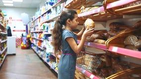 Το μικρό κορίτσι με την ψηφιακή ταμπλέτα στο μανάβικο αγοράζει τα προϊόντα αρτοποιίας ζυμών ψωμιού on-line μικρό κορίτσι φιλμ μικρού μήκους