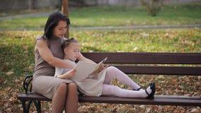 Το μικρό κορίτσι με τη θέση φακίδων με το mom κάθεται σε έναν πάγκο στο πάρκο Ευτυχής οικογένεια που διαβάζει ένα βιβλίο από κοιν απόθεμα βίντεο