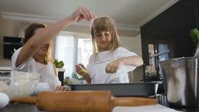 Το μικρό κορίτσι με τη μητέρα ψεκάζει τη σκόνη ζάχαρης πέρα από τα βουτύρου μπισκότα Μια νέα γυναίκα και λίγη κόρη ψήνουν μέσα απόθεμα βίντεο