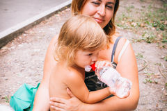 Το μικρό κορίτσι με τη σγουρή χρυσή ευχαρίστηση τρίχας πίνει το νερό για Στοκ Φωτογραφίες