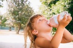 Το μικρό κορίτσι με τη σγουρή χρυσή ευχαρίστηση τρίχας πίνει το νερό για Στοκ Εικόνα