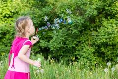 Το μικρό κορίτσι με τις πλεξίδες φυσά τις φυσαλίδες σαπουνιών Στοκ Φωτογραφία