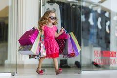 Το μικρό κορίτσι με τις τσάντες αγορών πηγαίνει στο κατάστημα στοκ φωτογραφία με δικαίωμα ελεύθερης χρήσης