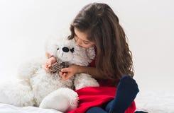 Το μικρό κορίτσι με το παιχνίδι βελούδου αντέχει στοκ φωτογραφία