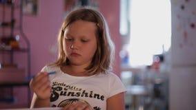 Το μικρό κορίτσι ξανθό σύρει ένα μπλε μολύβι στο υπόβαθρο - θολωμένη κουζίνα απόθεμα βίντεο
