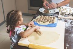 Το μικρό κορίτσι ξεδιπλώνει τη ζύμη, ενώ η μητέρα της sculpts οι μπουλέττες για τις διακοπές Στοκ φωτογραφία με δικαίωμα ελεύθερης χρήσης