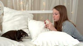 Το μικρό κορίτσι ο έφηβος fotogorafirut ένα κουνέλι στο smartphone Το κορίτσι παίρνει την εικόνα φωτογραφιών μέσω του έξυπνου τηλ απόθεμα βίντεο