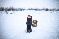 Το μικρό κορίτσι οδήγησε το έλκηθρο whith μια κόκκινη γάτα στο χιόνι στοκ φωτογραφία με δικαίωμα ελεύθερης χρήσης