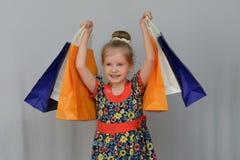 Το μικρό κορίτσι, ο αγοραστής κρατά τις χρωματισμένες τσάντες αγορών Στοκ εικόνες με δικαίωμα ελεύθερης χρήσης