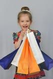 Το μικρό κορίτσι, ο αγοραστής κρατά τις χρωματισμένες τσάντες αγορών Στοκ Φωτογραφίες