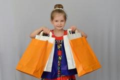 Το μικρό κορίτσι, ο αγοραστής κρατά τις χρωματισμένες τσάντες αγορών Στοκ Εικόνες