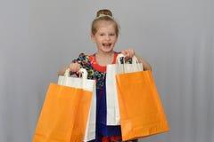 Το μικρό κορίτσι, ο αγοραστής κρατά τις χρωματισμένες τσάντες αγορών Στοκ Φωτογραφία