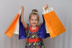 Το μικρό κορίτσι, ο αγοραστής κρατά τις χρωματισμένες τσάντες αγορών Στοκ εικόνα με δικαίωμα ελεύθερης χρήσης
