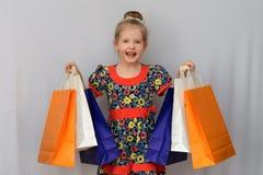 Το μικρό κορίτσι, ο αγοραστής κρατά τις χρωματισμένες τσάντες αγορών Στοκ φωτογραφία με δικαίωμα ελεύθερης χρήσης