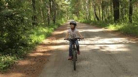 Το μικρό κορίτσι οδηγά το ποδήλατό της σε ένα δασικό ίχνος απόθεμα βίντεο