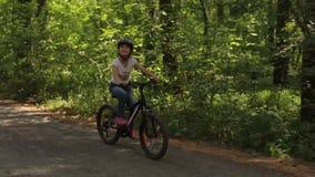 Το μικρό κορίτσι οδηγά το ποδήλατό της σε ένα δασικό ίχνος φιλμ μικρού μήκους