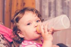 Το μικρό κορίτσι πίνει το γάλα από ένα μπουκάλι Στοκ Εικόνες