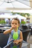 Το μικρό κορίτσι πίνει τη λεμονάδα με τη μέντα Στοκ Εικόνες