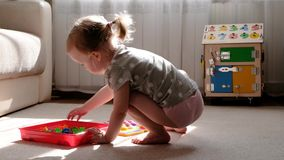 Το μικρό κορίτσι παίζει ένα παιχνίδι της ανάπτυξης των δεξιοτήτων μηχανών, συλλέγει ένα πολύχρωμο μωσαϊκό σχεδιαστών για τα παιδι φιλμ μικρού μήκους