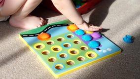 Το μικρό κορίτσι παίζει ένα παιχνίδι της ανάπτυξης των δεξιοτήτων μηχανών, συλλέγει ένα πολύχρωμο μωσαϊκό σχεδιαστών για τα παιδι απόθεμα βίντεο