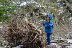 Το μικρό κορίτσι παίζει με το παλαιό κολόβωμα Στοκ Φωτογραφίες