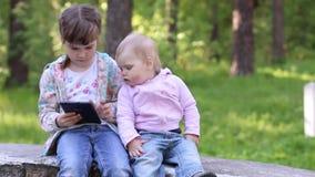 Το μικρό κορίτσι παίζει με το PC ταμπλετών και άλλο μικρό κορίτσι εξετάζει το απόθεμα βίντεο