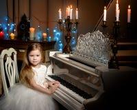 Το μικρό κορίτσι παίζει το πιάνο από το φως ιστιοφόρου στοκ εικόνες