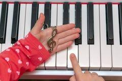 Το μικρό κορίτσι παίζει το πιάνο Τα χέρια του μουσικού στο πιάνο κλειδώνουν παίζοντας το όργανο Συναυλία της κλασικής μουσικής στοκ φωτογραφία