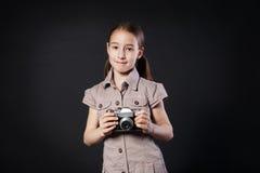 Το μικρό κορίτσι παίρνει τη φωτογραφία με την εκλεκτής ποιότητας κάμερα στο μαύρο υπόβαθρο Στοκ Φωτογραφία