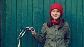 Το μικρό κορίτσι παιδιών στο κόκκινο καπέλο με το ποδήλατο δίπλα στον μπλε ναυτικό τοίχο κλείνει το μάτι με το μάτι της απόθεμα βίντεο