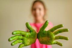 Το μικρό κορίτσι παρουσιάζει χέρια που χρωμάτισαν το πράσινο χρώμα στοκ εικόνες