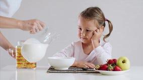 Το μικρό κορίτσι περιμένει τα δημητριακά προγευμάτων της με το γάλα φιλμ μικρού μήκους