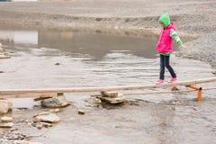 Το μικρό κορίτσι πηγαίνει προσεκτικά εν πλω πέρα από τη λίμνη Στοκ Εικόνες