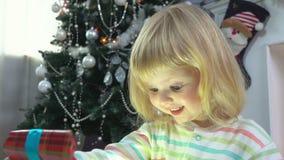 Το μικρό κορίτσι που δίνεται ένα χριστουγεννιάτικο δώρο κοντά στο χριστουγεννιάτικο δέντρο απόθεμα βίντεο