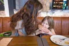 Το μικρό κορίτσι που δαγκώνει τη μητέρα της παραδίδει το εστιατόριο Στοκ εικόνες με δικαίωμα ελεύθερης χρήσης