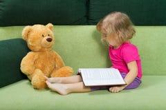 Το μικρό κορίτσι που διαβάζει ένα βιβλίο Teddy αντέχει στοκ εικόνα
