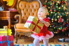 Το μικρό κορίτσι που κρατά ένα μεγάλο δώρο τύλιξε το χρυσό έγγραφο στοκ εικόνα με δικαίωμα ελεύθερης χρήσης