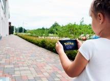 Το μικρό κορίτσι που παίζει ένα Pokemon πηγαίνει παιχνίδι υπαίθρια Στοκ Εικόνες