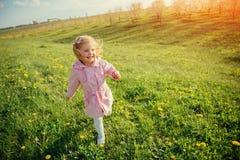 Το μικρό κορίτσι που τρέχει την άνοιξη την ηλιόλουστη ημέρα Επεξεργασία τέχνης Στοκ Φωτογραφία