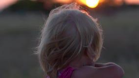 Το μικρό κορίτσι προσέχει το ηλιοβασίλεμα Το παιδί θαυμάζει τον ήλιο ρύθμισης το βράδυ απόθεμα βίντεο