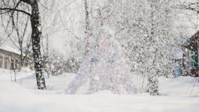 Το μικρό κορίτσι ρίχνει επάνω σε ένα χιόνι φιλμ μικρού μήκους